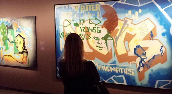 une jeune femme observe avec attention une oeuvre de graffiti / street art sur toile