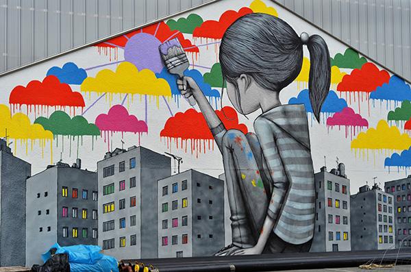 Enfant de dos apportant de la couleur du bout de son pinceau dans un paysage urbain morose