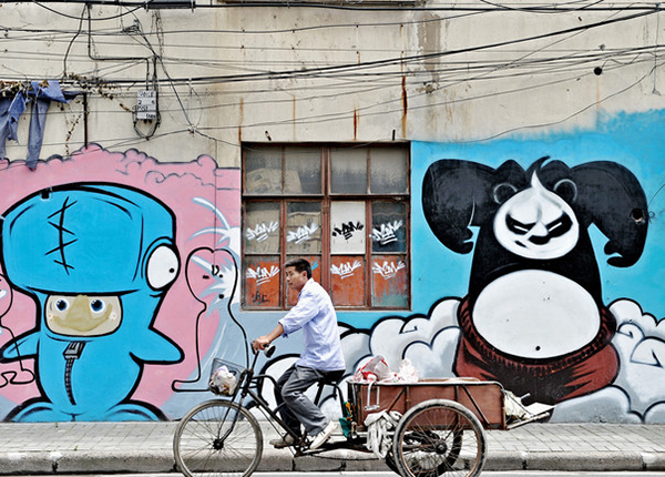 A man rides a tricycle past a wall paint