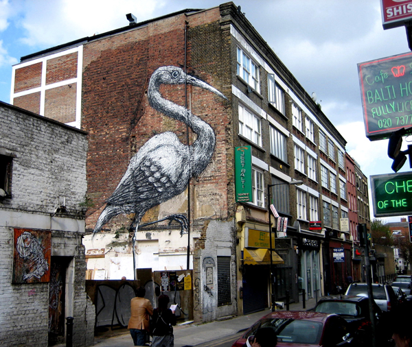 Peinture monumentale d'une cigogne dans la rue