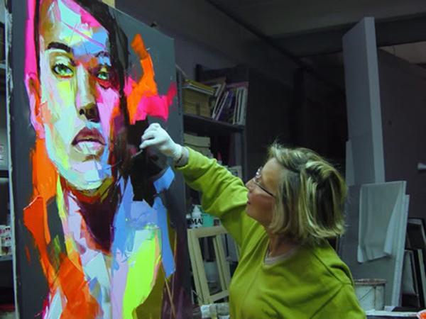 Vue de l'artiste française peingant un visage sur une toile
