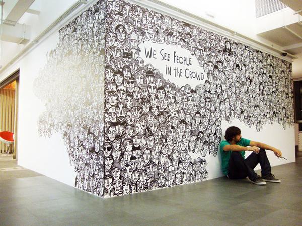 jeune homme assis devant un mur décoré en noir et blanc