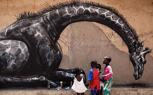 Des enfants africains jouent devant une pièce de Roa