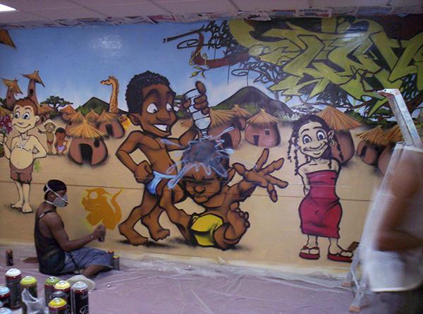 graffeur peignant un village africain sur un mur