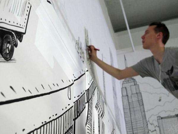 Graffeur de profil dessinant sur un mur blanc