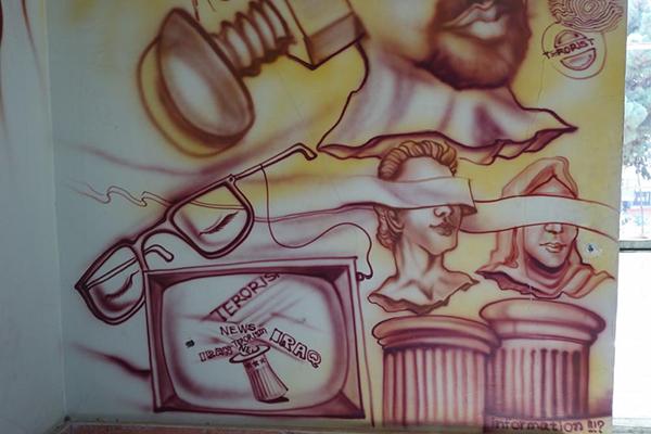Morceau d'une fresque graffiti questionnant sur le système d'information