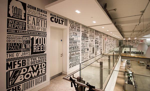 Des typos en noir et blanc recouvrent les murs à l'étage des locaux