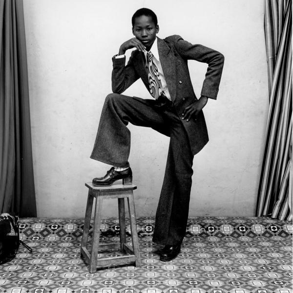 Jeune homme posant fièrement en costard cravate devant Sidibé