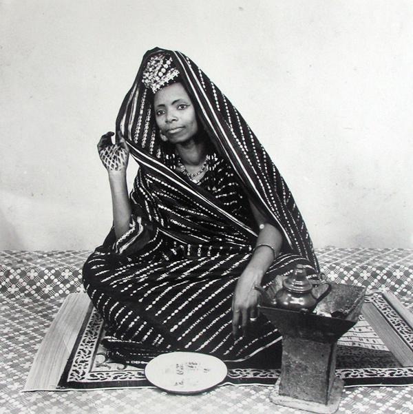 Une femme portant des habits traditionnels est assise et pose avec son thé